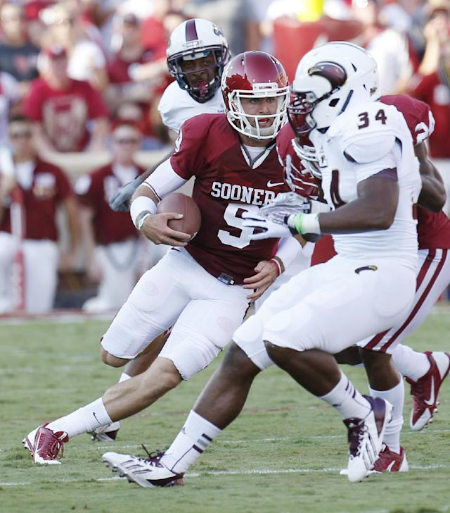 Oklahoma quarterback Trevor Knight (9)cuts between Louisiana Monroe defenders Darius Lively, left, and Michael Johnson (34) as he carries in the first quarter of an NCAA college football game in Norman, Okla., Saturday, Aug. 31, 2013. (AP Photo/Sue Ogrocki)
