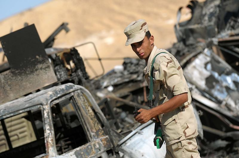Egyptian soldiers inspect the site of an attack on July 20, 2014, a day after 22 border guards where killed close to the El-Farafrah checkpoint near the border with Libya