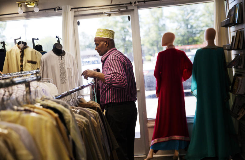 Mohamoud Saed, a refugee from Somalia, helps out in a friend's clothing store in Clarkston, Ga., Tuesday, May 2, 2017. Saed, who was a doctor in Somalia before he fled the nation's civil war, anxiously awaits the arrival of his wife and eight children while struggling with kidney issues that he hopes could be solved with a transplant from one of his family members. The Saeds completed the lengthy refugee application process but never made the trip to the U.S. Their travel documents expired during legal wrangling over President Donald Trump's executive orders to limit the refugee program and ban travel from several countries, including Somalia. (AP Photo/David Goldman)