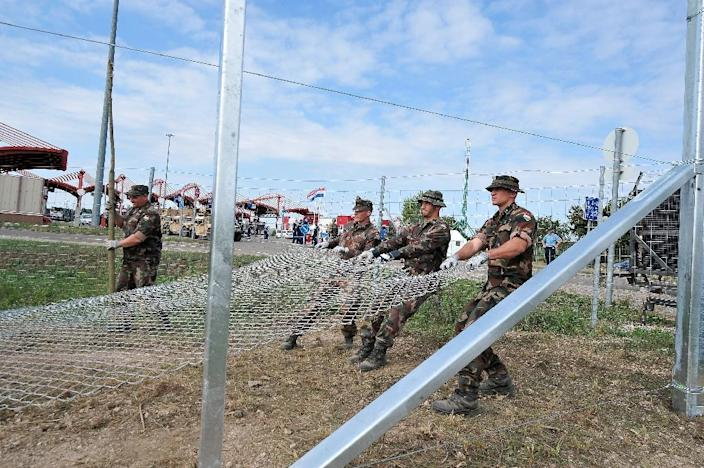 Hungarian soldiers, seen from the Croatian side, raise fences at the Croatian-Hungarian border crossing between the villages of Baranjsko Petrovo Selo, Croatia, and Beremend, Hungary, on September 22, 2015 (AFP Photo/Elvis Barukcic)