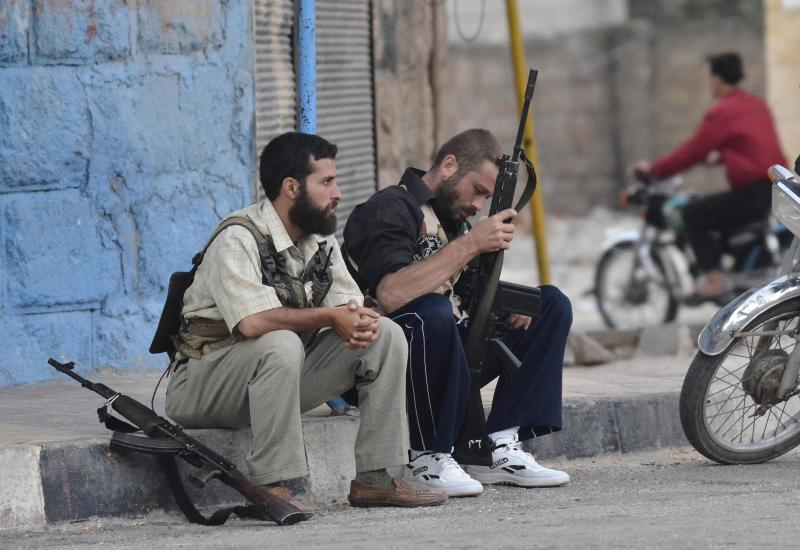 Free Syrian Army soldiers sit on a sidewalk at the northern town of Sarmada, in Idlib province, Syria, Wednesday, Aug. 1, 2012. (AP Photo)