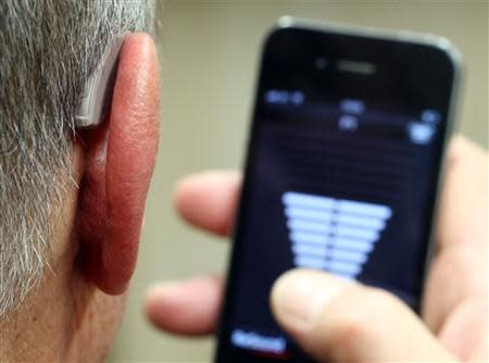 An employee of GN, the world's fourth largest maker of hearing aids, demonstrates the use of ReSound LiNX in Vienna November 22, 2013. REUTERS/Heinz-Peter Bader