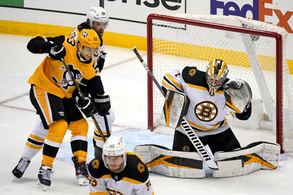 Boston Bruins goaltender Jeremy Swayman (1) gloves a shot with Kevan Miller (86) defending Pittsburgh Penguins' Teddy Blueger (53) during the first period of an NHL hockey game in Pittsburgh, Sunday, April 25, 2021.(AP Photo/Gene J. Puskar)
