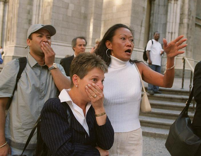 People in front of New York's St. Patrick's Cathedral react with horror as they look down Fifth Ave towards the World Trade Center towers after planes crashed into their upper floors Tuesday morning, Sept. 11, 2001. Explosions and fires collapsed the 110-story buildings. (AP Photo/Marty Lederhandler)