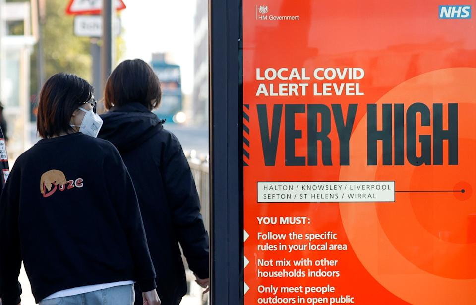 A person wearing a protective mask walks past a covid warning sign as the spread of the coronavirus disease (COVID-19) continues, in Liverpool, Britain October 15, 2020. REUTERS/Phil Noble