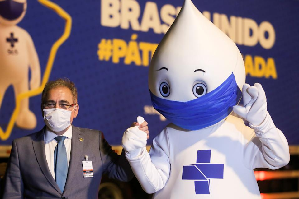 Brazil's Minister of Health, Marcelo Queiroga, poses for a photo with the mascot Ze Gotinha, symbol of Brazilian vaccination campaigns as doses of Pfizer-BioNTech vaccines against the coronavirus disease (COVID-19) arrives at Viracopos International Airport, in Campinas, Brazil April 29, 2021. REUTERS/Amanda Perobelli