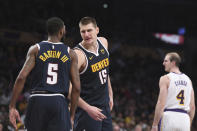 Denver Nuggets center Nikola Jokic (15) talks with forward Will Barton III (5) after Jokic was fouled during the second half of an NBA basketball game against the Los Angeles Lakers Sunday, Dec. 22, 2019, in Los Angeles. The Nuggets won 128-104. (AP Photo/Michael Owen Baker)