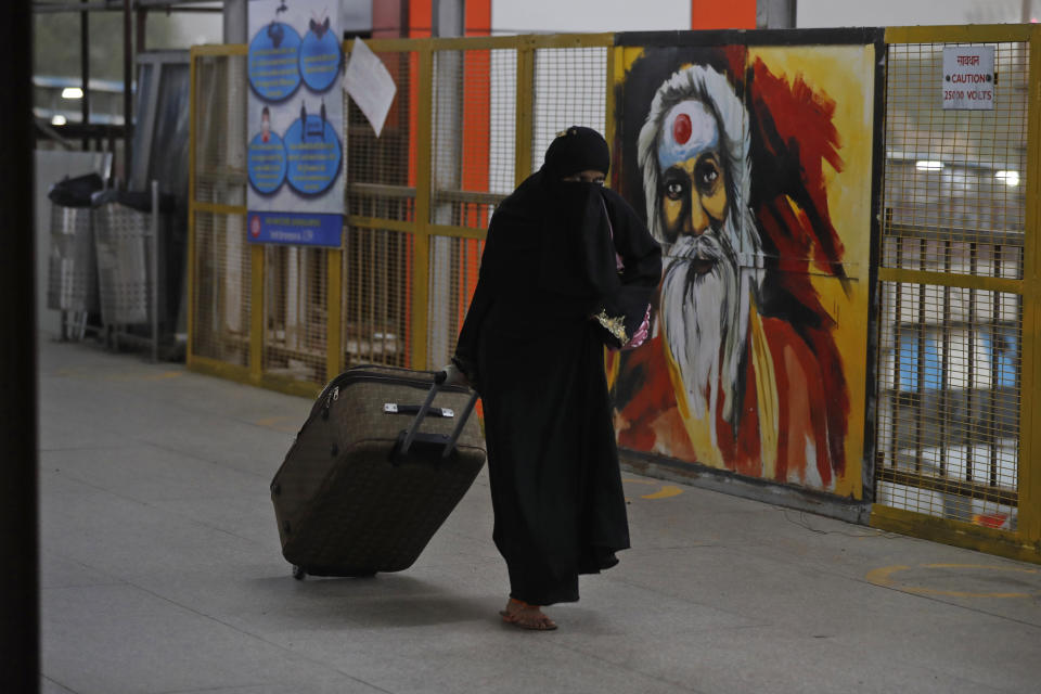 A migrant laborer walks with her belongings after arriving from Maharashtra state, in Prayagraj, India, Saturday, May 30, 2020. India is extending the ongoing lockdown in containment zones till June 30 but will allow all economic activities to restart in a phased manner outside these areas even though coronavirus cases continue to rise in its major cities. The upcoming reopening phase which will start Monday is called Unlock 1, the home ministry said in a directive Saturday. (AP Photo/Rajesh Kumar Singh)