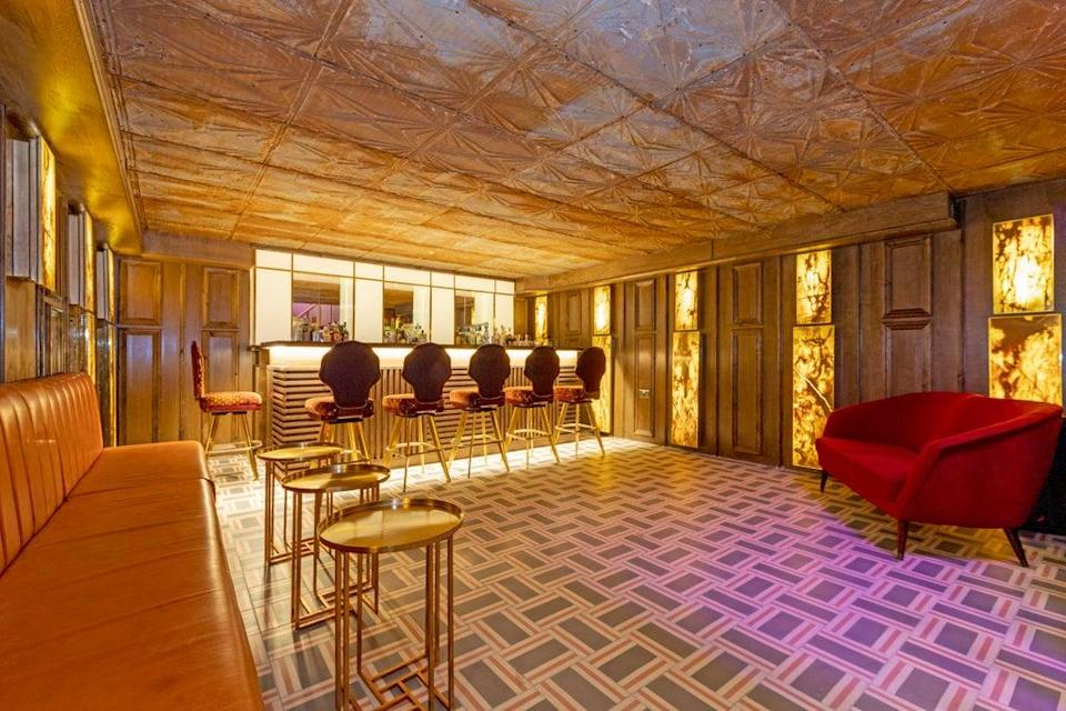 New addition: a six-seater, gold gilded bar has panelled walls and sheets of marble lights (Dexters)
