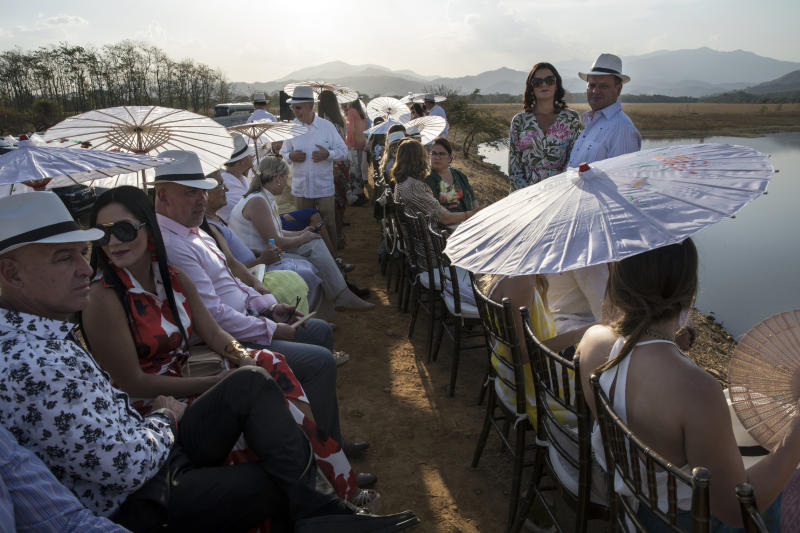 In this Feb. 16, 2019 photo, guests wait for the arrival of groom Juan Jose Pocaterra and his bride Maria Fernanda Vera to their wedding in Acarigua, Venezuela. Women wore long dresses and used colorful umbrellas and folding fans to keep cool under the sun; men followed the recommended attire of white shirts, suspenders and beige pants, and donned Panama hats provided by the organizers. (AP Photo/Rodrigo Abd)