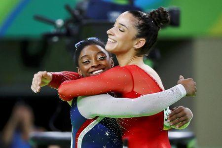 Simone Biles and Alexandra Raisman celebrate winning gold and silver respectively at the women's individual all-around final. REUTERS/Mike Blake