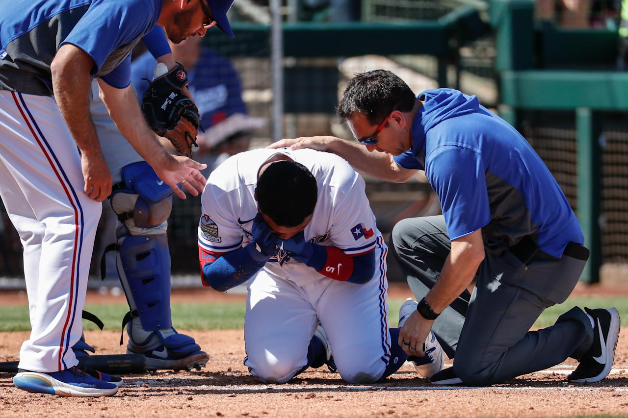 SURPRISE, AZ - MARCH 08:  Texas Rangers left fielder Willie Calhoun (5) grabs his face after he's hit by a pitch during the spring training MLB baseball game between the Los Angeles Dodgers and the Texas Rangers on March 8, 2020 at Surprise Stadium in Surprise, Arizona. (Photo by Kevin Abele/Icon Sportswire via Getty Images)