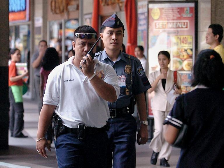 Policemen patrol in suburban Manila on February 16, 2005