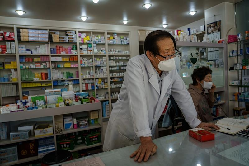 Lee Jong-ho, a pharmacist, works behind the counter in Chuncheon.