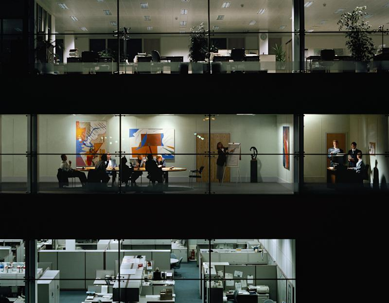 Executives in meeting, view through windows of office block at night