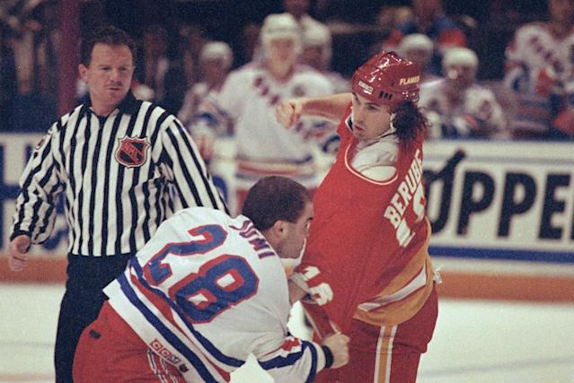 FILE - In this Jan. 16, 1992, file photo, Calgary Flames' Craig Berube readies to throw a punch at New York Rangers' Tie Domi during during first period action at New York's Madison Square Garden. Berube accumulated 3,149 penalty minutes, seventh all time, as an NHL player from 1986-2004. Domi accumulated 3,515 penalty minutes in his playing career from 1989-2006, third all time. The fights that were as much a part of the blood-smeared fabric of the game and had hardcore fans whipped into a frenzy all around North America with bouts more worthy of the squared circle are melting from the ice. (AP Photo/Ron Frehm, File)