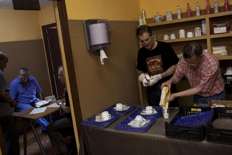 Volunteers, right, prepare breakfast as men, left, wait their turn to receive their daily ration of food in Caliu, a charity site in Barcelona, Spain, Tuesday June 5, 2012. More than one hundred people are fed every day in Caliu as part of a charity program created by local volunteers and neighbors to help unemployed and people without financial resources. The Spanish economy is in recession for the second time in three years as the damage from a housing bust persists. Foreclosures are rising, Spain's banks are in worse financial shape and the government's deficit is hitting worrisome levels. (AP Photo/Emilio Morenatti)