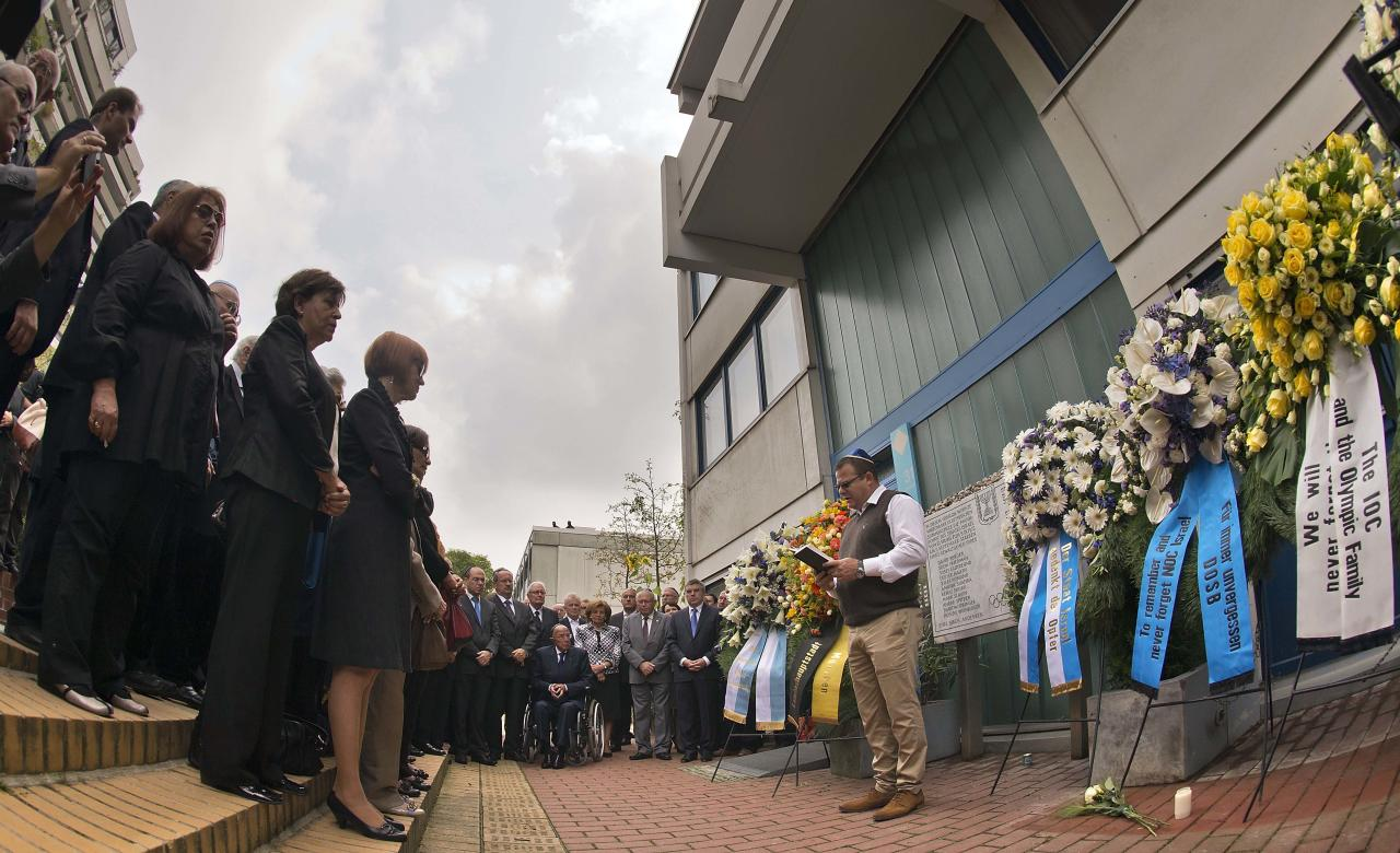 Shay Shapira, son of murdered athletics trainer Amitzur Shapira, right, delivers a speech in front of wreaths at a memorial at the former accommodation of the Israeli Olympic team in Munich, southern Germany, Wednesday, Sept. 5, 2012, during a commemoration ceremony for the assassination victims of the Olympic games in Munich in 1972. 17 people died in a failed liberation attempt of Israeli hostages, eleven of them of Israel's Olympic team, five terrorists and a German police officer. (AP Photo/dapd, Joerg Koch)