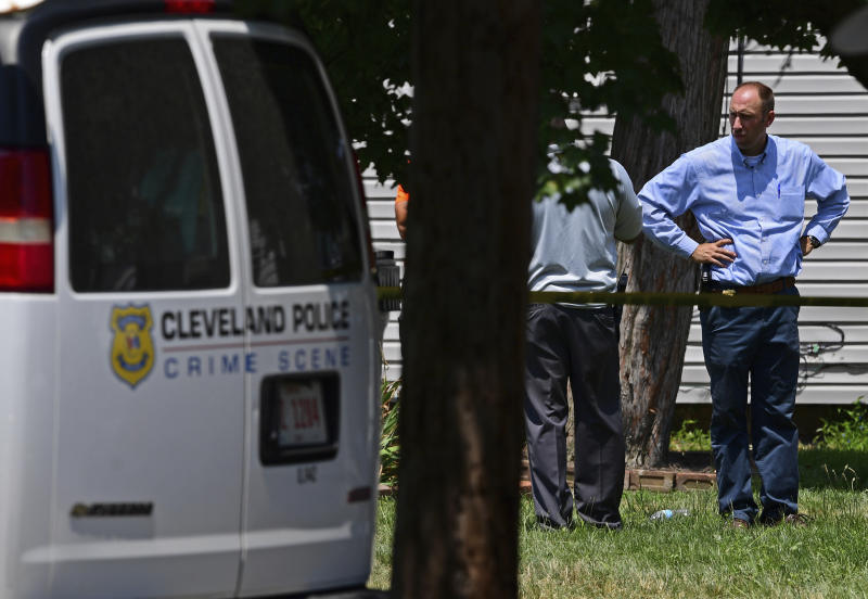 Police officers work at the scene where several bodies were found, Tuesday, July 9, 2019, in Cleveland. Police investigating the shooting death of a man in a vacant lot say they also found the bodies of a woman and two children in a nearby house. Authorities aren't saying how the three found inside the house Tuesday died, but they did say the four deaths are connected. (AP Photo/David Dermer)