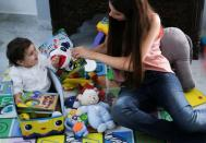 Emmanuelle Lteif Khnaisser, who was in labour at the moment of last year's Beirut port blast, plays with her son baby George Khnaisser, at the family home in Jal el-Dib