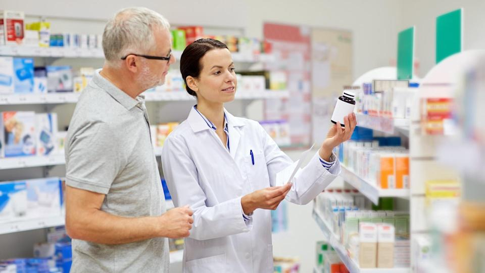 medicine, pharmaceutics, health care and people concept - happy pharmacist and senior man customer with drug and prescription at drugstore.