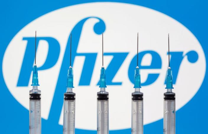 FILE PHOTO: Syringes are seen in front of a displayed Pfizer logo in this illustration