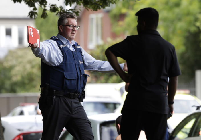 <p>A police officer attempts to move people away from across the road from a mosque in central Christchurch, New Zealand. (AP Photo/Mark Baker) </p>