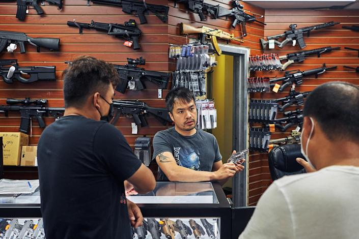 """Jimmy Gong, co-owner of Jimmy's Sportshop in Mineola, N.Y., shows a revolver to customers on July 10, 2021.<span class=""""copyright"""">An Rong Xu for TIME</span>"""