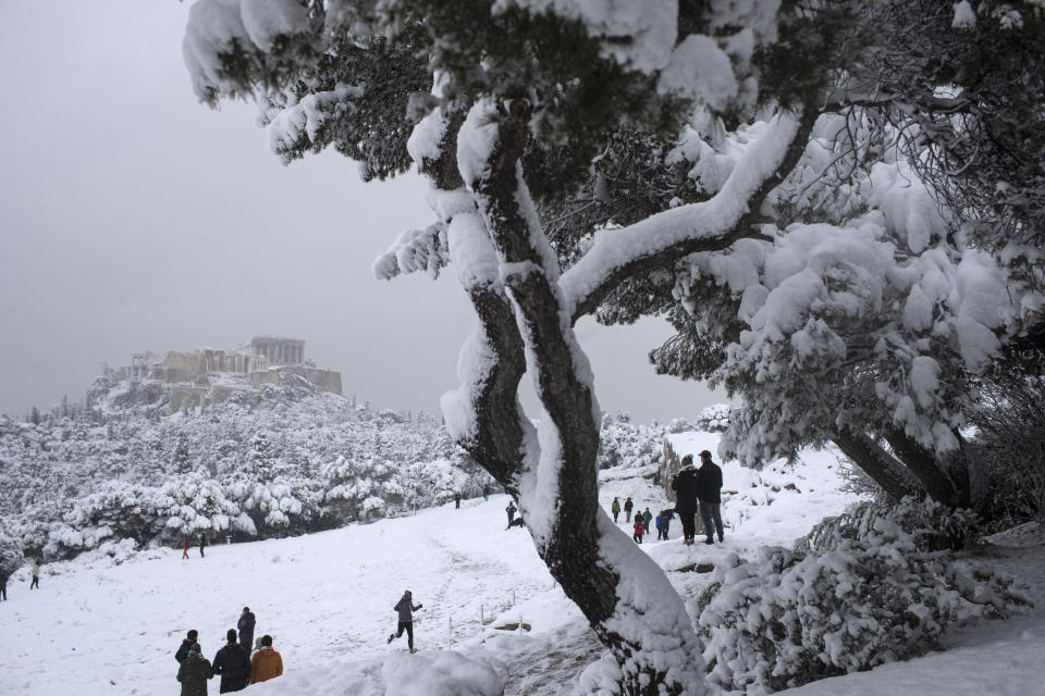People play in the snow at Filopapos Hill in front the ancient Acropolis hill with the ruins of the fifth century B.C. Parthenon temple, in Athens, on Tuesday, Feb. 16, 2021. Unusually heavy snowfall has blanketed central Athens, with authorities warning residents particularly in the Greek capital's northern and eastern suburbs to avoid leaving their homes. (AP Photo/Petros Giannakouris)