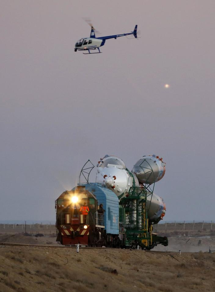 Russian police helicopter guards Russia's Soyuz-FG booster rocket with the space capsule Soyuz TMA-11M that will carry new crew to the International Space Station (ISS), as the rocket is transported from hangar to the launch pad at the Russian leased Baikonur cosmodrome, Kazakhstan, Tuesday, Nov. 5, 2013. The rocket is scheduled to blast off on Thursday, Nov.7. (AP Photo/Dmitry Lovetsky)