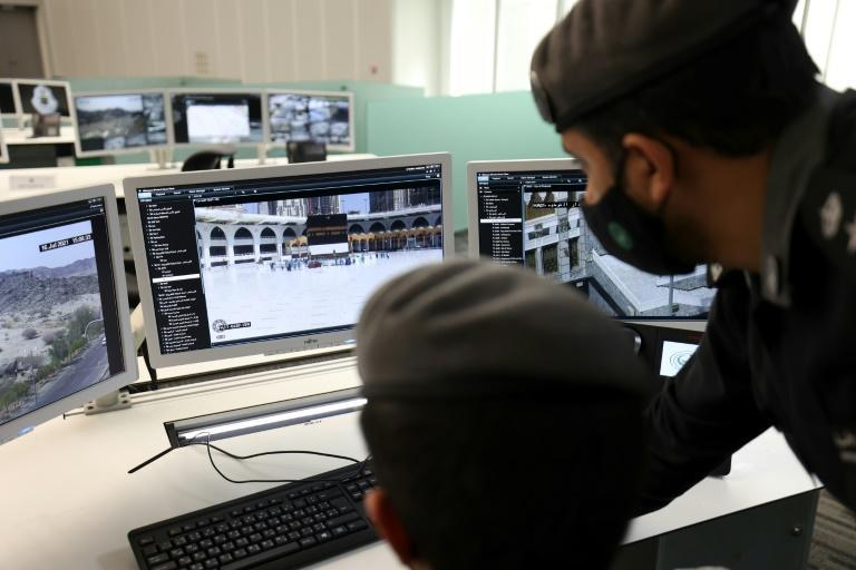 Mask-clad members of the Saudi security forces monitor on screens the streets and religious sites of the holy city of Meccca, on July 16, the eve of the start of the annual hajj pilgrimage