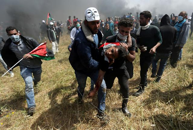 <p>A wounded Palestinian demonstrator is evacuated during clashes with Israeli troops at the Israel-Gaza border at a protest demanding the right to return to their homeland, in the southern Gaza Strip, April 6, 2018. (Photo: Ibraheem Abu Mustafa/Reuters) </p>