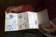 Alejandro Perez, 31, shows his Saint James pilgrim's credential after receiving a stamp at the end of a stage in Najera, near Pamplona, northern Spain, Thursday, April 15, 2021. The pilgrims are trickling back to Spain's St. James Way after a year of being kept off the trail due to the pandemic. Many have committed to putting their lives on hold for days or weeks to walk to the medieval cathedral in Santiago de Compostela in hopes of healing wounds caused by the coronavirus. (AP Photo/Alvaro Barrientos)