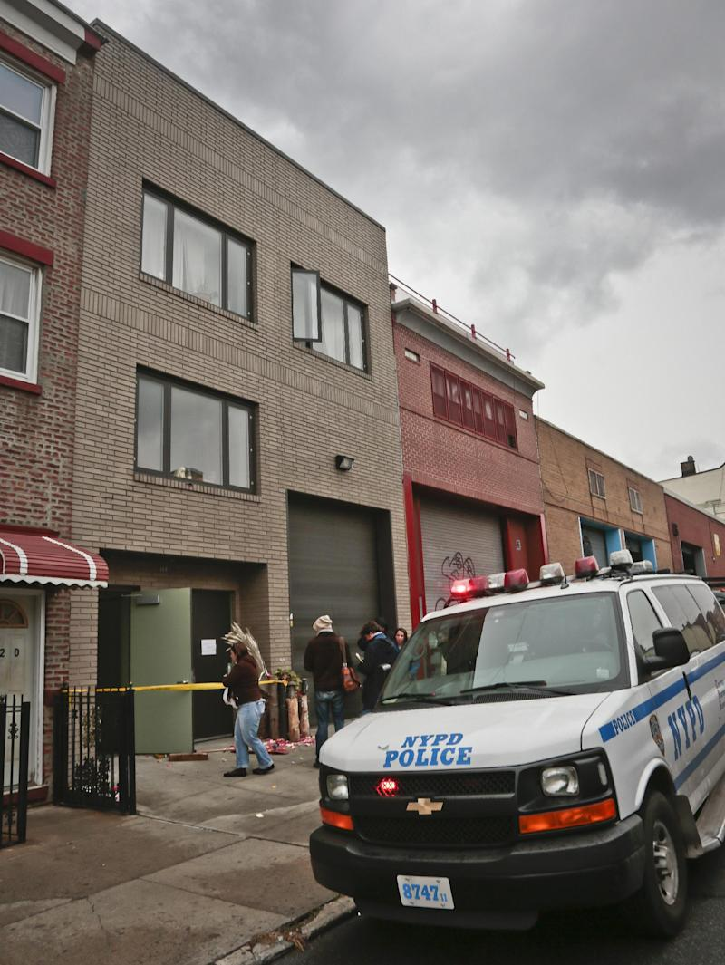 """A police vehicle parks outside the location of a Monday shooting rampage, Tuesday, Nov. 12, 2013 in Brooklyn, New York. Police said gunman Ali Akbar Mahammadi Rafie, 29, a musician, killed himself on the roof after shooting to death two members of the Iranian indie rock band Yellow Dogs, a third musician and wounding a fourth person early Monday morning. The shooter was a member of another band from Iran, the Free Keys, who knew the victims but hadn't spoken to them in months because of a """"petty conflict,"""" according to Yellow Dogs manger Ali Salehezadeh. (AP Photo/Bebeto Matthews)"""