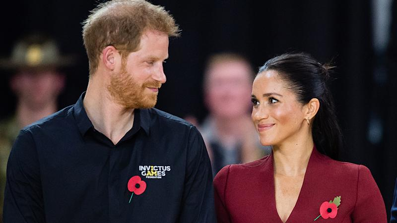 Prince Harry and Meghan Markle smile at each other with remembrance day roses