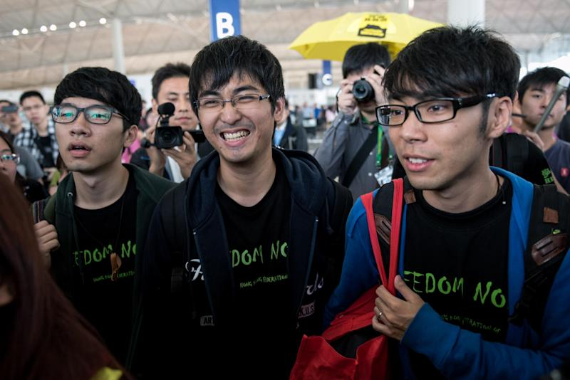 Hong Kong student leaders Nathan Law (left), Alex Chow (centre) and Eason Chung are surrounded by pro-democracy protesters at Hong Kong's international airport before an attempt to board a flight to Beijing, on November 15, 2014