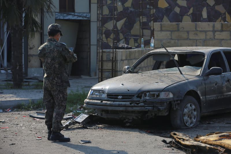 A man stands in front of a damaged car following shelling in Barda