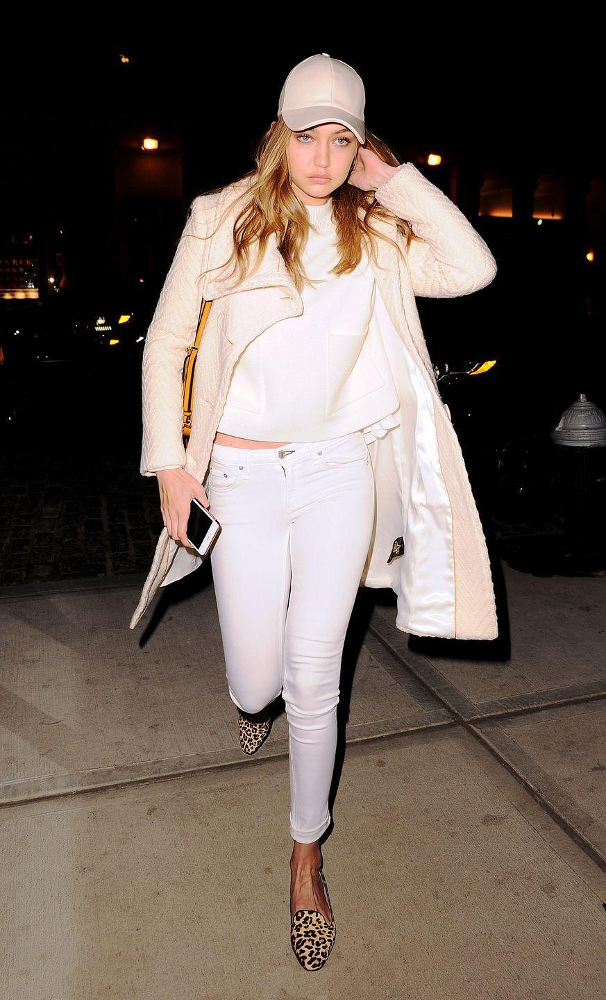 <p>The model steps out in an all-white ensemble, complete with a midi coat and a leather baseball hat. </p>
