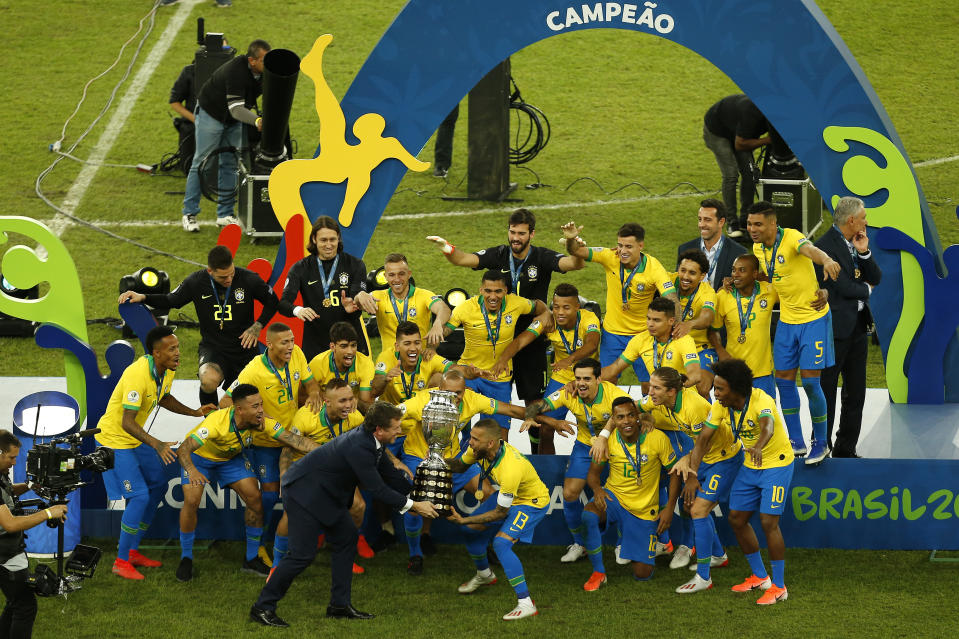 Brazil's Dani Alves celebrates with the trophy and his teammates after Copa America final win over Peru