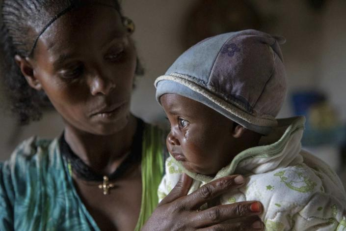 """Mother Ababa, 25, comforts her baby Wegahta, 6 months, who was identified as severely acutely malnourished, in Gijet in the Tigray region of northern Ethiopia Tuesday, July 20, 2021. For months, the United Nations has warned of famine in Tigray and now internal documents and witness accounts reveal the first starvation deaths since Ethiopia's government in June imposed what the U.N. calls """"a de facto humanitarian aid blockade."""" (Christine Nesbitt/UNICEF via AP)"""