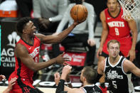 Houston Rockets forward Jae'Sean Tate, left, shoots as Los Angeles Clippers center Ivica Zubac, low center, defends along with guard Luke Kennard, lower right, during the first half of an NBA basketball game Friday, April 9, 2021, in Los Angeles. (AP Photo/Mark J. Terrill)