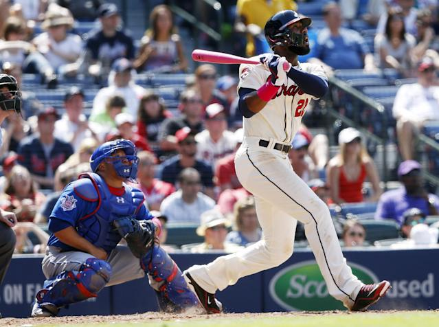 Atlanta Braves' Jason Heyward, right, follows through on a two-run home run as Chicago Cubs catcher Welington Castillo, left, looks on in the seventh inning of a baseball game on Sunday, May 11, 2014, in Atlanta. (AP Photo/John Bazemore)