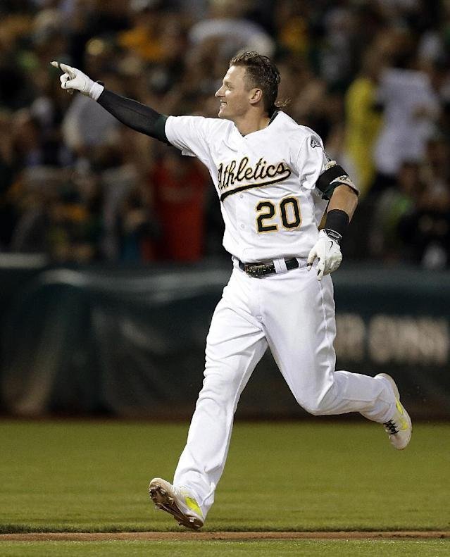 Oakland Athletics' Josh Donaldson celebrates after hitting the game-winning three-run home run off Baltimore Orioles' Zach Britton in the ninth inning of a baseball game Friday, July 18, 2014, in Oakland, Calif. Oakland won 5-4. (AP Photo/Ben Margot)