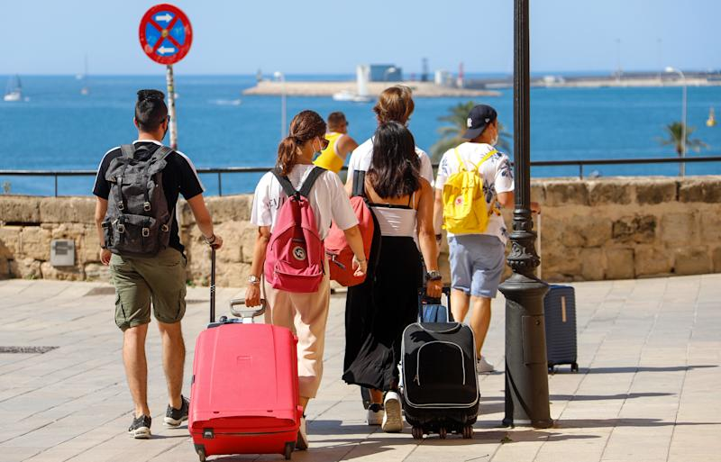 26 July 2020, Spain, Palma: People walk through the city with their wheeled suitcases. Holidaymakers returning to Germany from abroad can have themselves tested for the virus free of charge on their return. Photo: Clara Margais/dpa (Photo by Clara Margais/picture alliance via Getty Images)
