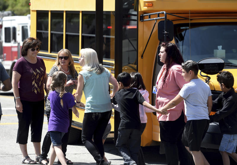 In this April 10, 2017, photo, North Park Elementary teaching assistant Jennifer Downing, right, evacuates the building with students after a shooting occurred at the school in San Bernardino, Calif. Downing said she thinks the shooter, Cedric Anderson, would have killed others if he hadn't run out of bullets and stopped to reload Monday. Anderson fatally shot himself after killing his estranged wife, teacher Karen Elaine Smith, and an 8-year-old boy, Jonathan Martinez, in a special-education classroom at North Park Elementary. (John Valenzuela/The Press-Enterprise via AP)