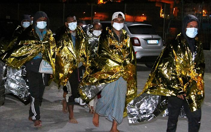 Migrants, wrapped in emergency thermal blankets, arriving on Lampedusa - Reuters