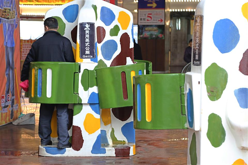 A man uses the public street urinal next to the recreational facilities at Foreigners' Street on March 15, 2017 in Chongqing, China. The public street urinals having no doors but small boards shielding men's waists appeared at Foreigners' Street in Chongqing. (Photo by Zuo Dongchen/VCG via Getty)