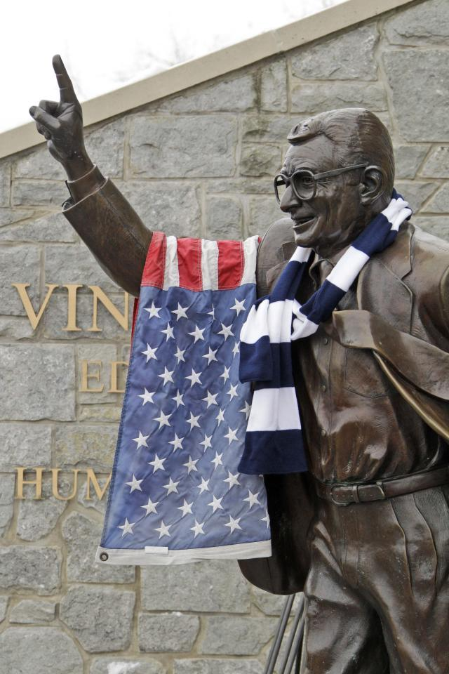 A flag and Penn State scarf are displayed on a statue of former Penn State football coach Joe Paterno outside Beaver Stadium on the Penn State campus as fans pay their respects after learning of Paterno's death Sunday, Jan. 22, 2012, in State College, Pa. (AP Photo/Gene J. Puskar)
