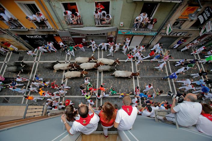 <p>JUL. 9, 2016 — Revellers run with Jose Escolar Gil's fighting bulls along Estafeta Street during the fourth day of the San Fermin Running of the Bulls festival in Pamplona, Spain. The annual Fiesta de San Fermin, made famous by the 1926 novel of US writer Ernest Hemmingway entitled 'The Sun Also Rises', involves the daily running of the bulls through the historic heart of Pamplona to the bull ring. (Pablo Blazquez Dominguez/Getty Images) </p>