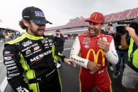 Bubba Wallace, front right, is congratulated by Ryan Blaney, left, after Wallace was pronounced the winner while on pit row during a rain delay in a NASCAR Cup series auto race Monday, Oct. 4, 2021, in Talladega, Ala. (AP Photo/John Amis)